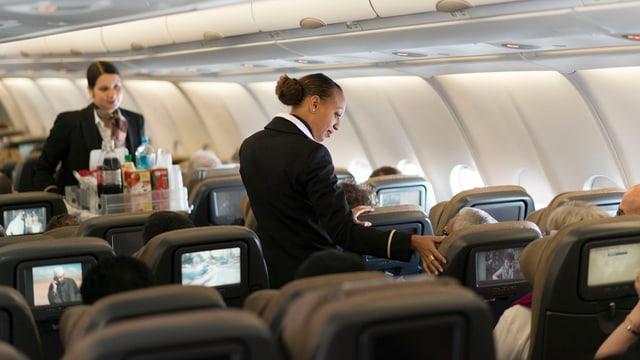 Persunal da la Swiss che discurran cun ils passagiers en l'aviun.