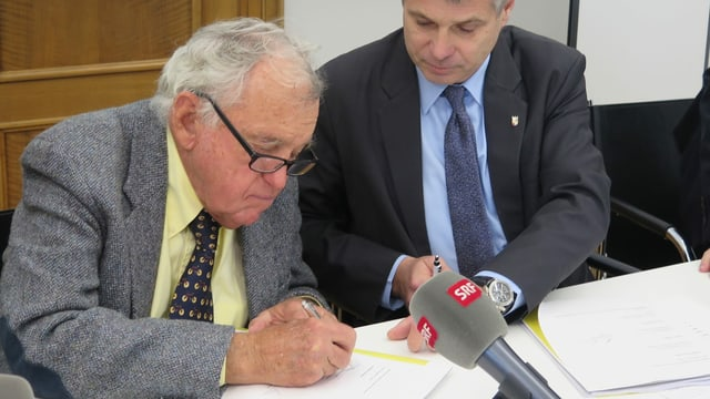 Hansjörg Wyss unterschreibt einen Vertrag