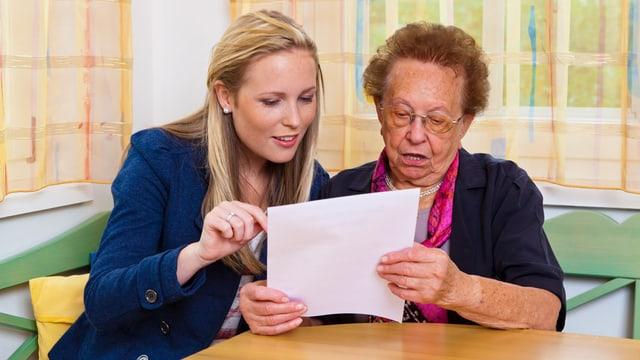 Eine ältere Frau liest mit einer jungen Frau ein Dokument durch.