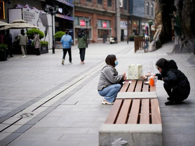 Frauen in Wuhan am Essen auf einer Bank