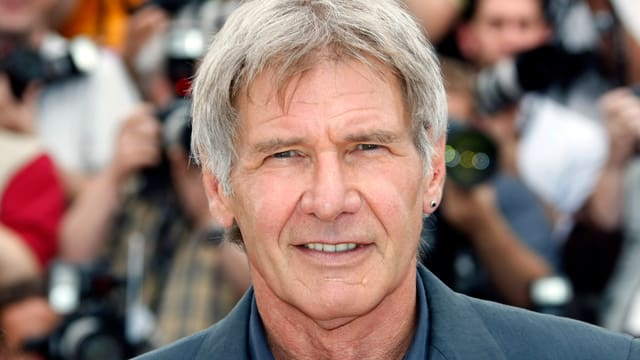Harrison Ford lacht in Kamera.