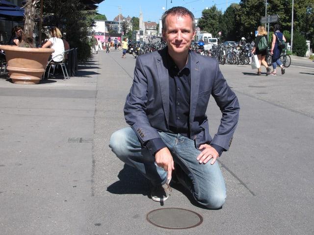 Swisscom-Mann Marco Bertossa zeigt auf den Deckel, unter dem die Mobilfunk-Antenne montiert ist.