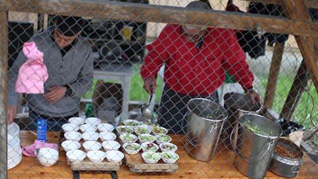 Menschen füllen Essen in Schalen.