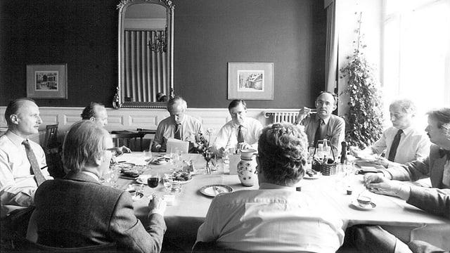 Mehrere Menschen sitzen an einem Tisch zusammen und diskutieren.