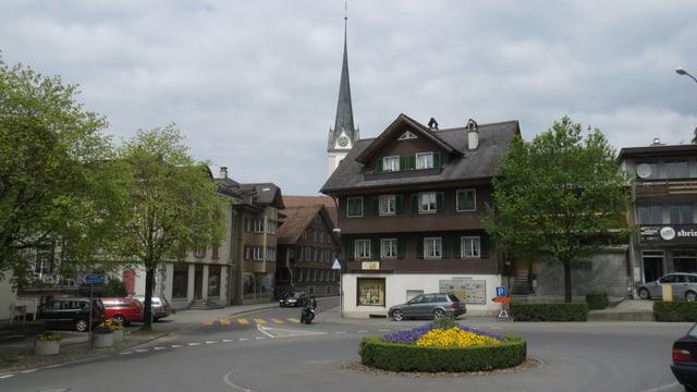Dorfplatz mit Kreisel, Häusern und Kirche.