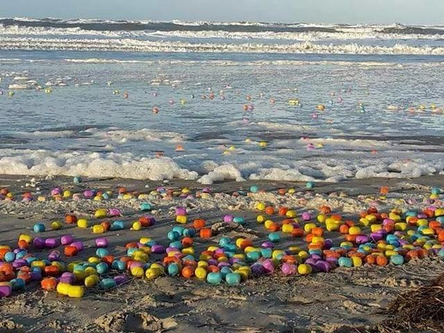 Hunderte Überraschungseier an Strand und in Meer.