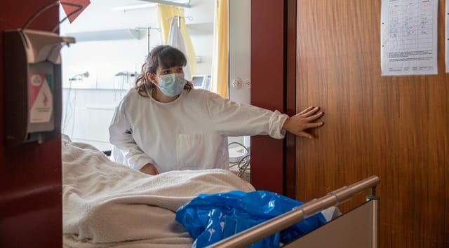 Aline Zehnder öffnet eine Tür. Sie schiebt einen Patienten in ein Zimmer.