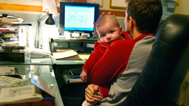 Ein Mann mit einem Kleinkind auf dem Schoss vor einem Computer