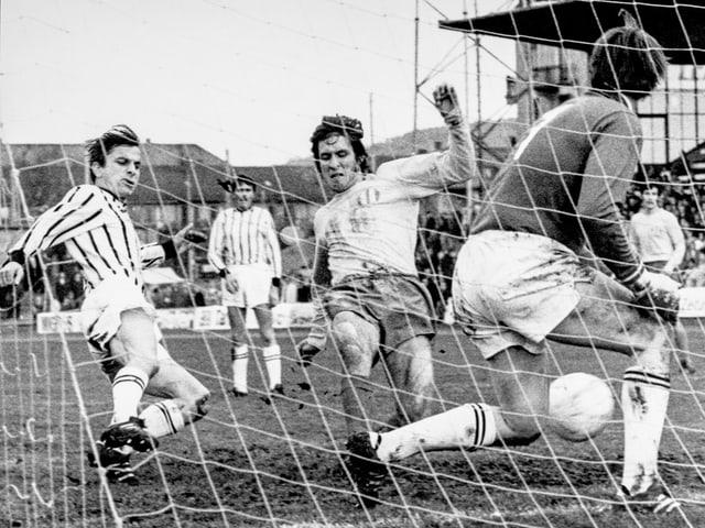 Schwarz-Weiss-Fotografie mit fünf Fussballspielern vor einem Tor.