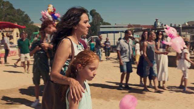 Auf einem Rummelplatz, im Hintergrund Menschen mit Ballons. Im Vordergrund eine Frau, die die Hand um ein Mädchen gelegt hat.