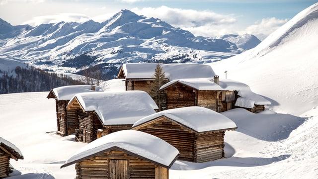 Bergdorf unter einer Schneedecke - Bergpanorama im Hintergrund.