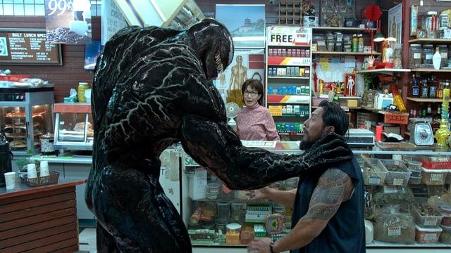 Der Alien Venom greift einen Mann an.