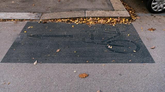 Ein übermaltes Velosymbol auf einer Strasse