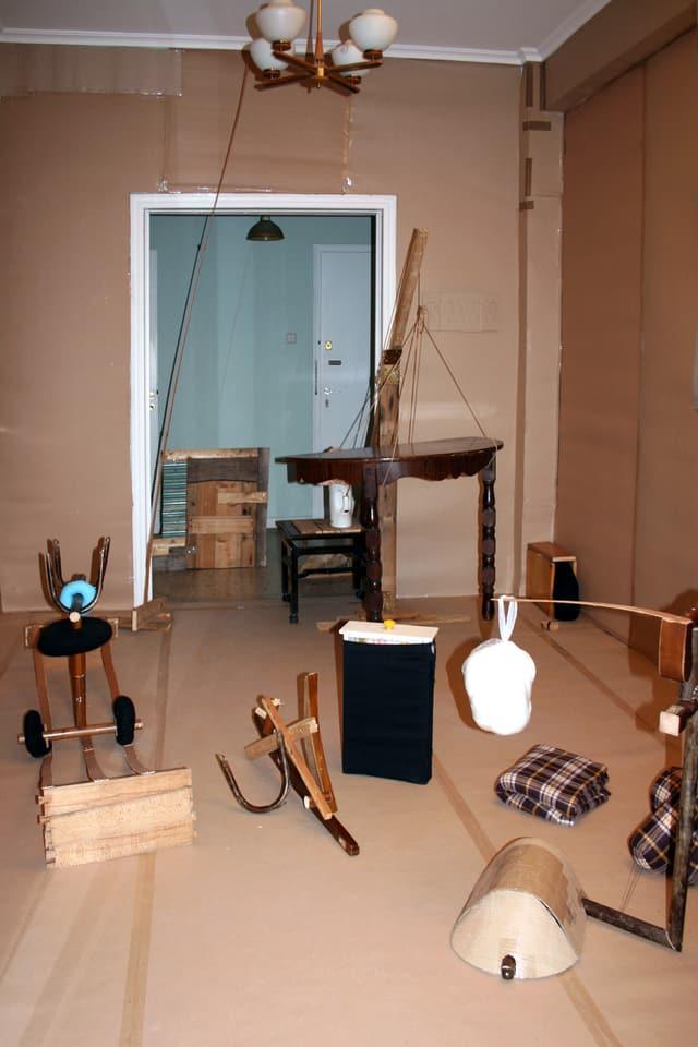 Fundgegenstände wie Decken, Holzbretter, Möbelteile und Geräte liegen in einer Wohnung, deren Boden und Wände mit Karton eingekleidet wurden.