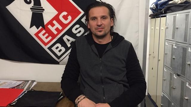 EHC-Trainer Peter Salmik vor einer Fahne des EHC Basel