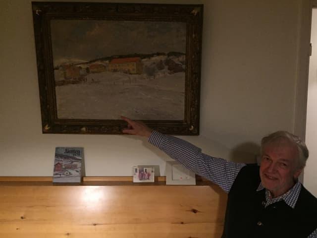 Heinz Erlbacher sitzt auf einem Holzbank und zeigt auf ein Gemälde.