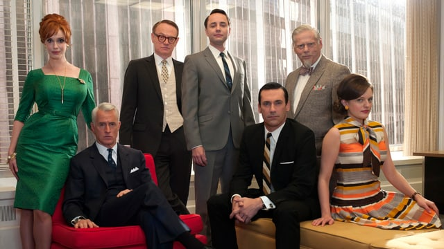 Vor einem grossen Fenster haben sich sieben Personen zu einem Gruppenfoto aufgestellt. Sie tragen alle Kleidung aus den 70er Jahren und auch die Zimmereinrichtung stammt aus dieser Zeit. Vor der Gruppe steht ein kleiner Tisch, auf dem ein Lifestyle-Magazin und ein gefüllter Aschenbecher stehen.