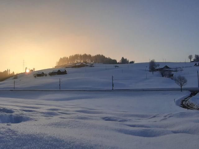 Die Sonne geht hinter einem verschneiten Hügel auf.