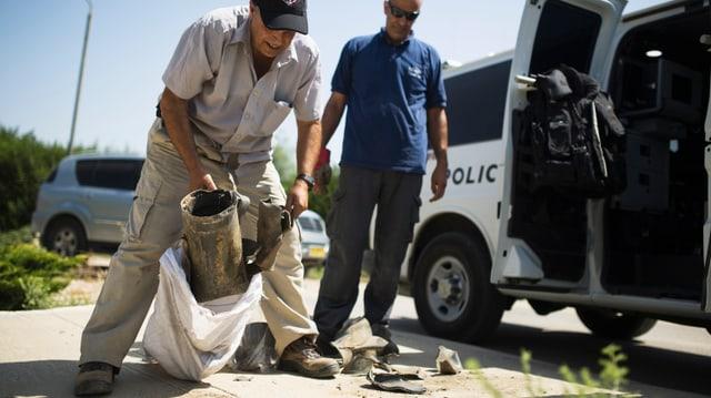 Zwei Männer, ein Polizeiauto, Trümmerteile einer Rakete.
