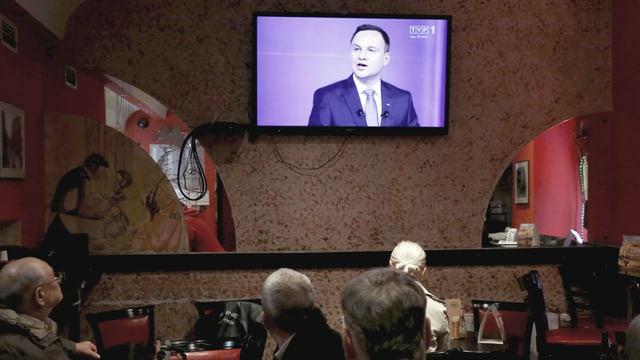 Polnische Männer sitzen vor einem Bildschirm, darauf zu sehen: Andrzej Duda von «Recht und Gerechtigkeit» beim TV-Duell vor den Wahlen 2015.
