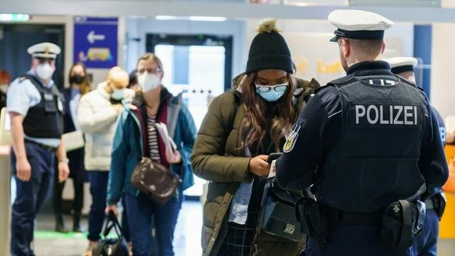 Polizisten kontrollieren Einreisende am Flughafen.