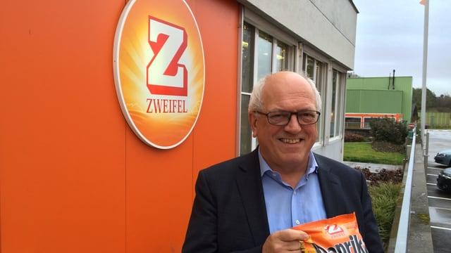 Adank mit einer Packung Paprika-Chips vor der Fabrik in Spreitenbach.