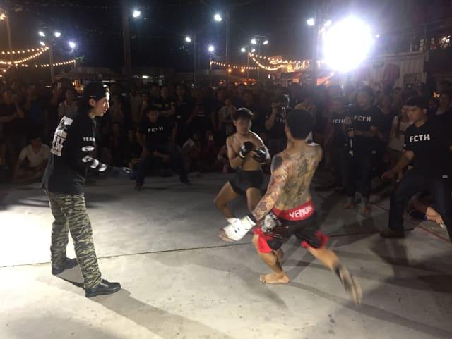 Zwei Kämpfer mit dünnen Handschuhen von Männern in schwarzen T-Shirts umgeben, die den Kampf überwachen und mit Handys filmen.