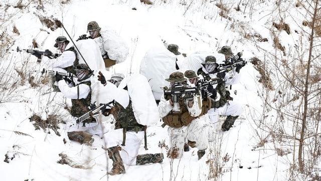 Soldaten in weissen Tarnanzügen operieren bewaffnet im Schnee.