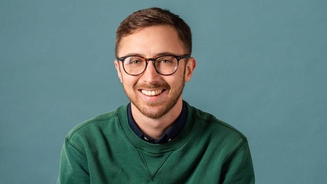 Ein junger Mann mit Brille, lächelnd.