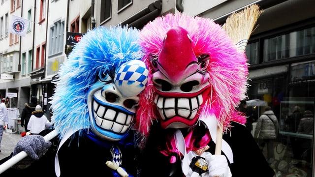 Zwei Basler Fasnächtler in Masken mit grosser Nase und Mund und bunten Haaren