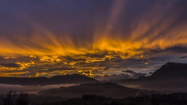 Blick über den Chiemen am Zugersee, Richtung Berge. Wildes Strahlenmeer über den Alpen.