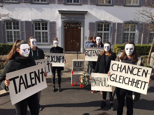 Sechs junge Leute, maskiert mit weissen Larven, protestieren.