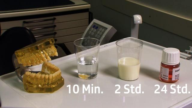 Künstliches Gebiss, daneben ein Glas Wasser, ein Glas kalte Milch und eine Zahnrettungsbox