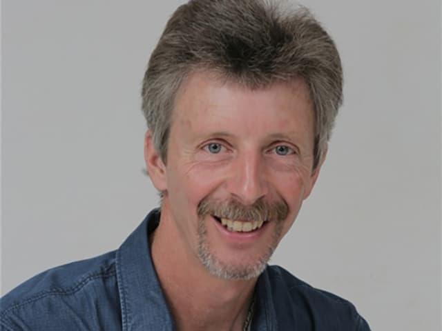 Porträt von einem Mann mit Schnurr- und Kinnbart.