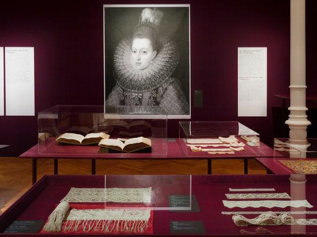 Schwarzweiss-Gemälde einer Dame mit Spitzenkragen, davor Ausstellungsstücke in Vitrinen
