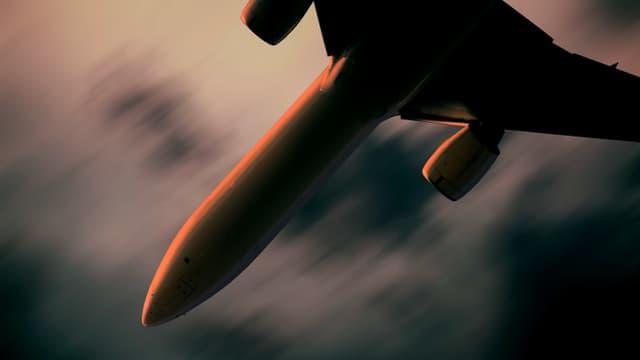 Bauchansicht eines Flugzeugs: Es fliegt durch einen dunklen Himmel.