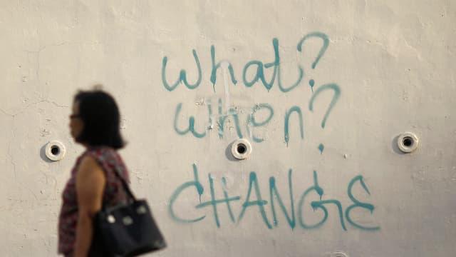 Eine Frau geht an einer Wand vorbei, auf der das Graffiti «What? When? Change?» steht.