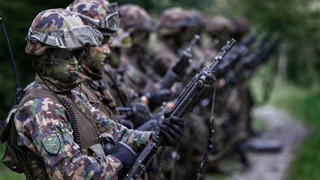 Schweizer Armee-Angehörige mit Waffe in der Hand.