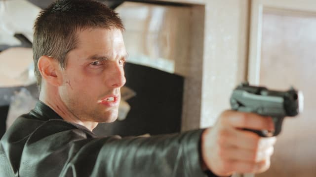 Tom Cruise als John Anderton hält eine Waffe auf etwas gerichtet.