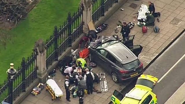 Beschädigtes Fahrzeug steht auf dem Fussgängerweg am Zaun zum Parlamentsgebäude.