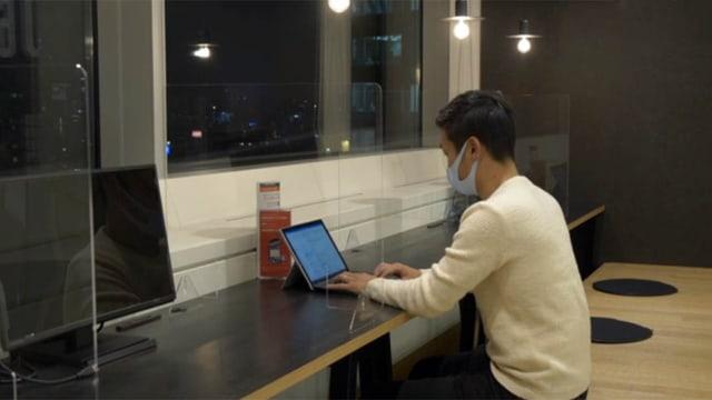 Japaner an einer langen Sitzbank mit Tablet