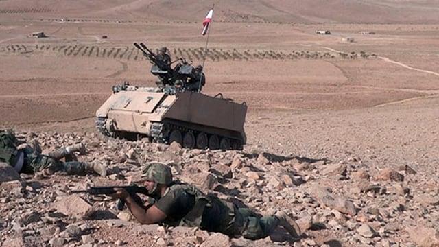 Soldat liegt mit Gewehr im Anschlag auf dem steinigen Wüstenboden, im Hintergrund ein Panzer mit einer Luftabwehrkanone