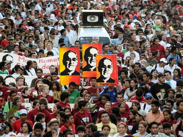 Menschen demonstrieren und halten Schilder mit dem Gesicht von Romero in die Höhe