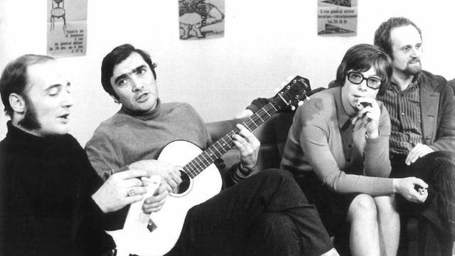 Drei Männer und eine Frau sitzen nebeneinander auf einem Sofa. Einer hält eine Gitarre in der Hand.