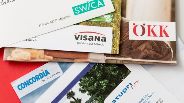Prospekte der ÖKK, Concordia, Visana, Swica und Atupri liegen auf einem Tisch.