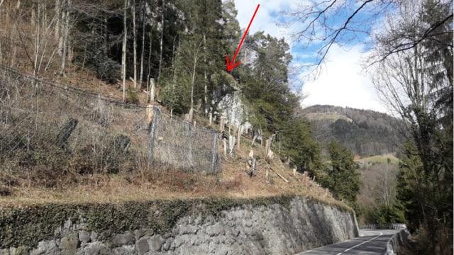 Unten verläuft eine Strasse, oben steht ein Fels in einem bewaldeten Hang.