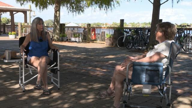 zwei Frauen sitzen auf Campingstühlen auf Promenade im Schatten