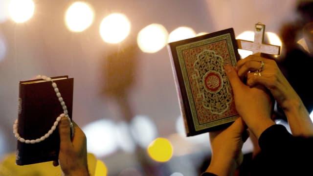Eine Hand hält links eine Bibel hoch, rechts hält eine Hand den Koran hoch.