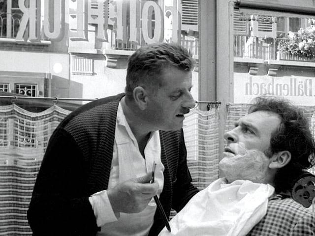 Ein Mann mit Rasiermesser in der Hand spricht mit einem Kunden, der Rasierschaum im Gesicht hat.