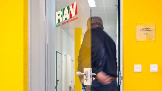 Ein Mann betritt das RAV durch eine Glastür. Die Wände am Eingang sind gelb.